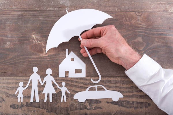 male hand holding an umbrella over a family, their home and car