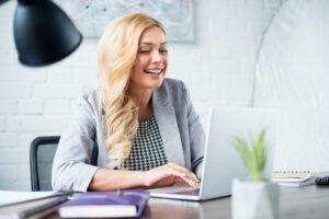 Smiling businesswoman using laptop at work
