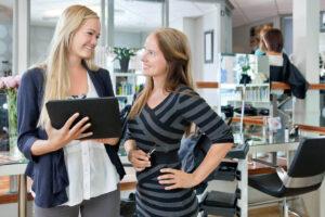 brunette female salon owner with blonde insurance agent on tablet