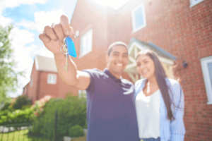 young couple holding the key outside of their new brick home