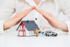 hands covering a model house, car, and family like a shield